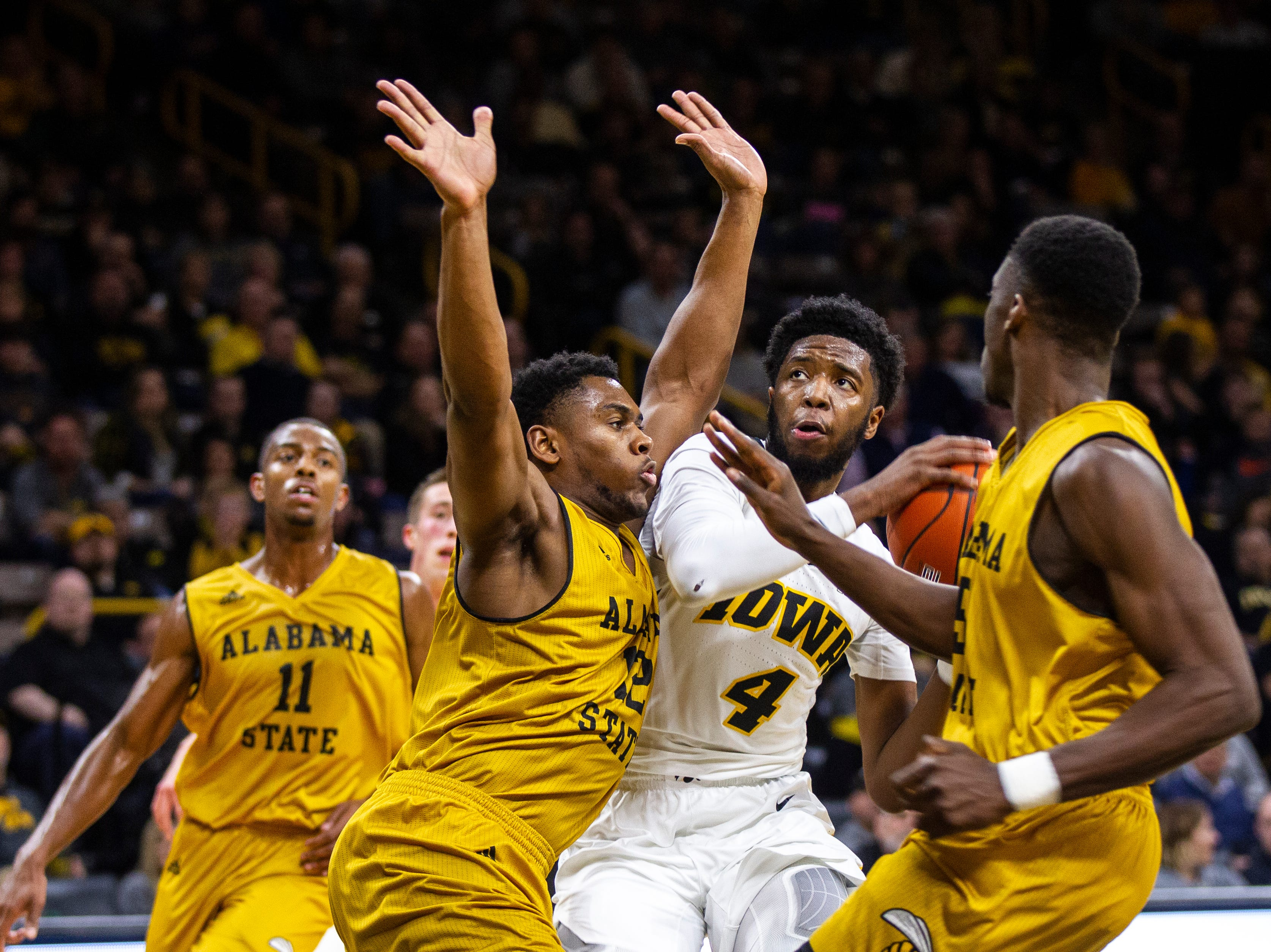 Iowa guard Isaiah Moss (4) attempts a shot in the paint while being defended by Alabama State's Reginald Gee (12) during an NCAA men's basketball game on Wednesday, Nov. 21, 2018, at Carver-Hawkeye Arena in Iowa City.