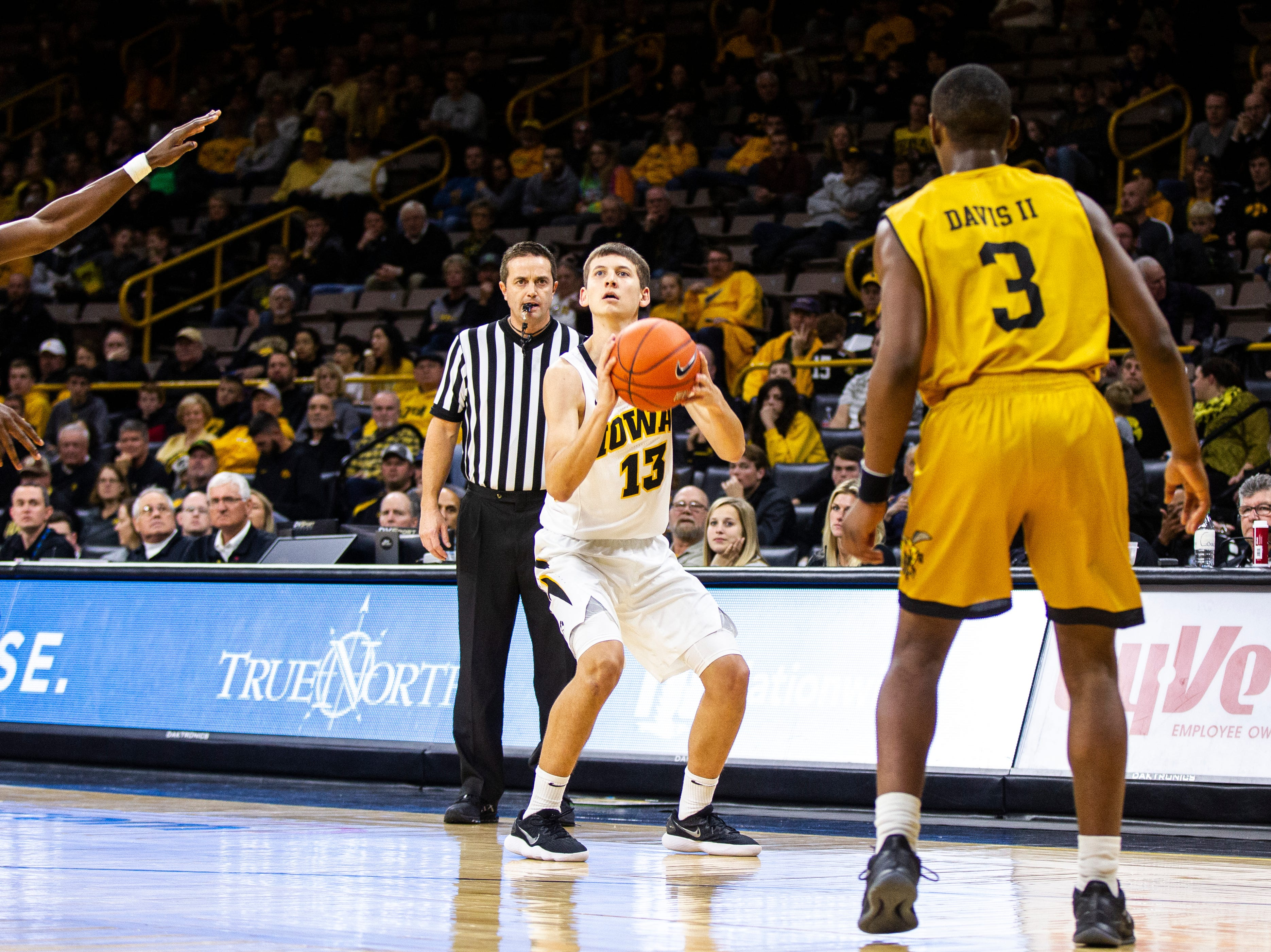 Iowa guard Austin Ash (13) shoots a 3-point basket during an NCAA men's basketball game on Wednesday, Nov. 21, 2018, at Carver-Hawkeye Arena in Iowa City.