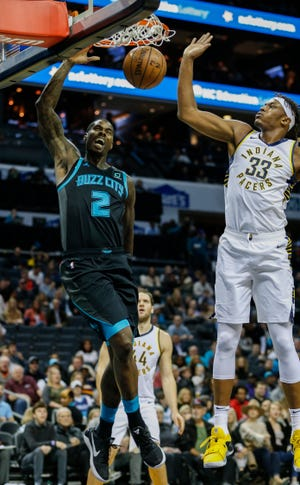 Charlotte Hornets forward Marvin Williams, left, dunks next to Indiana Pacers center Myles Turner during the first half of an NBA basketball game in Charlotte, N.C., Wednesday, Nov. 21, 2018.