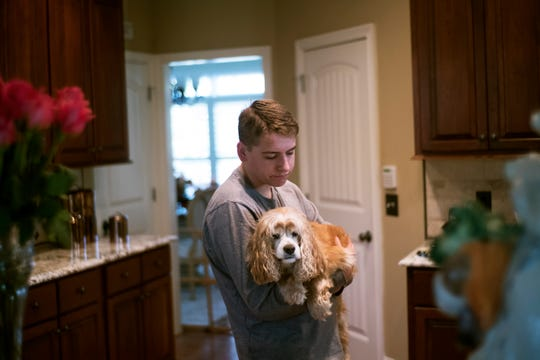 Riley Schrick holds his dog, BJ, at home in Lenoir City. Schrick, a former Farragut High School student, has been bullied relentlessly.