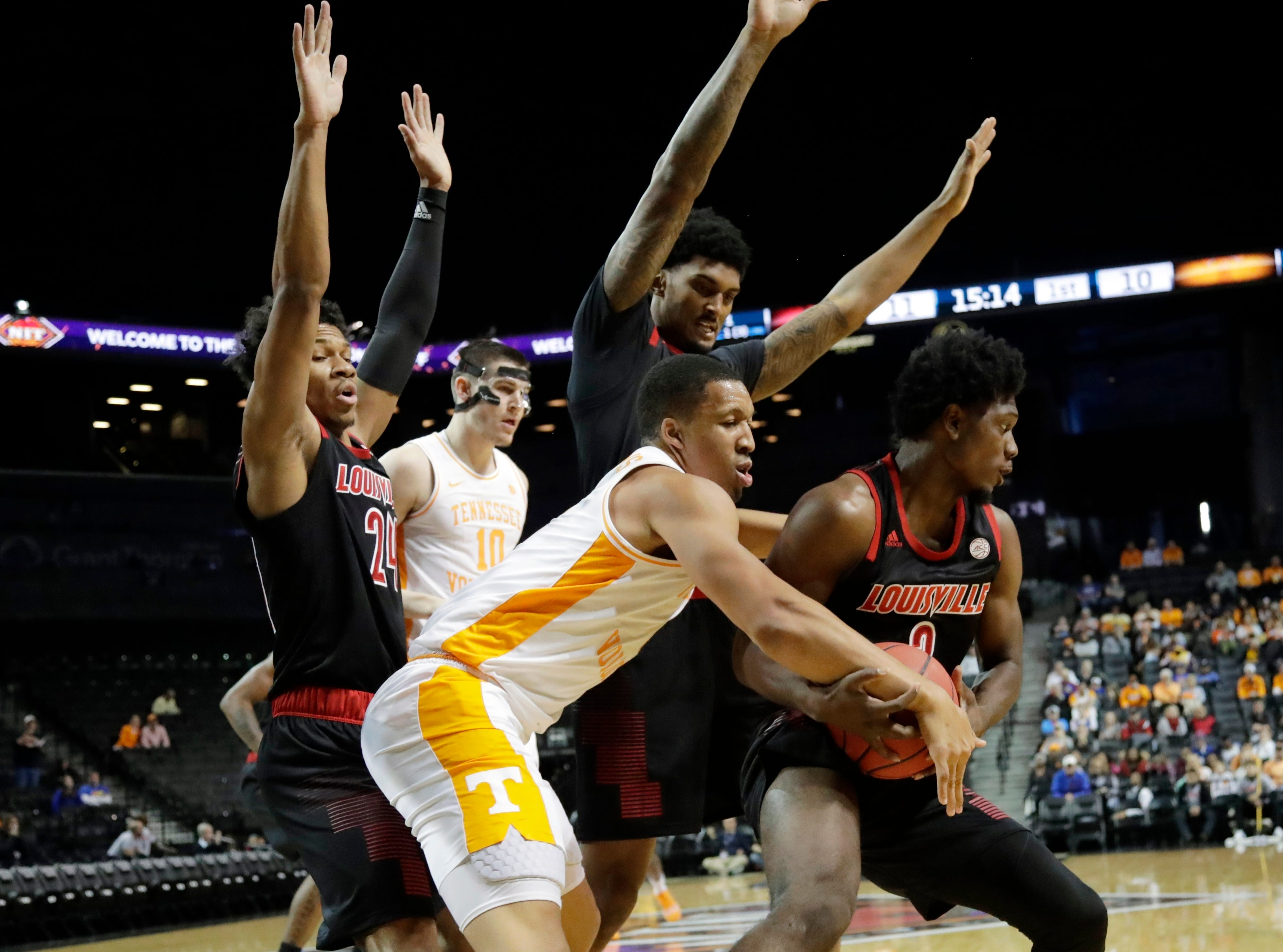Louisville's Darius Perry (2) and Tennessee's Grant Williams (2) fight for control of the ball as Dwayne Sutton (24) and John Fulkerson (10) watch during the first half of an NCAA college basketball game in the NIT Season Tip-Off tournament Wednesday, Nov. 21, 2018, in New York. (AP Photo/Frank Franklin II)