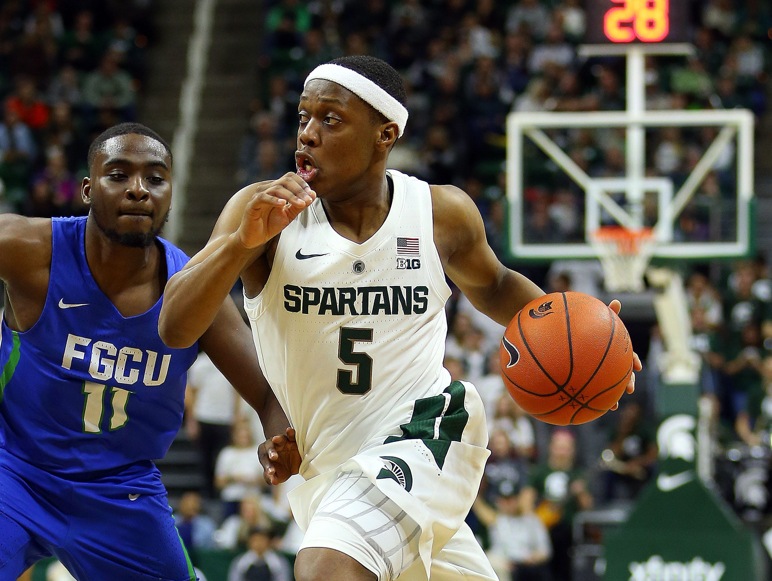 Nov 11, 2018; East Lansing, MI, USA; Michigan State Spartans guard Cassius Winston (5) drives past Florida Gulf Coast Eagles guard Schadrac Casimir (11) during the second half of a game at the Breslin Center. Mandatory Credit: Mike Carter-USA TODAY Sports