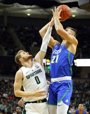Nov 11, 2018; East Lansing, MI, USA; Florida Gulf Coast Eagles forward Brady Ernst (21) shoots over Michigan State Spartans forward Kyle Ahrens (0) during the first half of a game at the Breslin Center. Mandatory Credit: Mike Carter-USA TODAY Sports