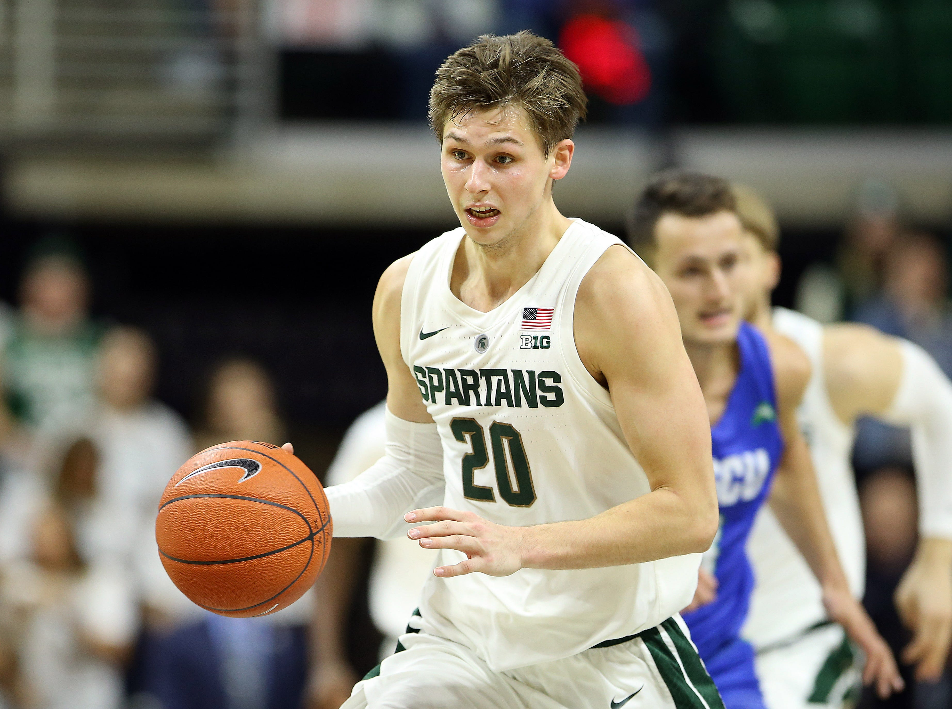 Nov 11, 2018; East Lansing, MI, USA; Michigan State Spartans guard Matt McQuaid (20) brings the ball up court against the Florida Gulf Coast Eagles during the second half of a game at the Breslin Center. Mandatory Credit: Mike Carter-USA TODAY Sports