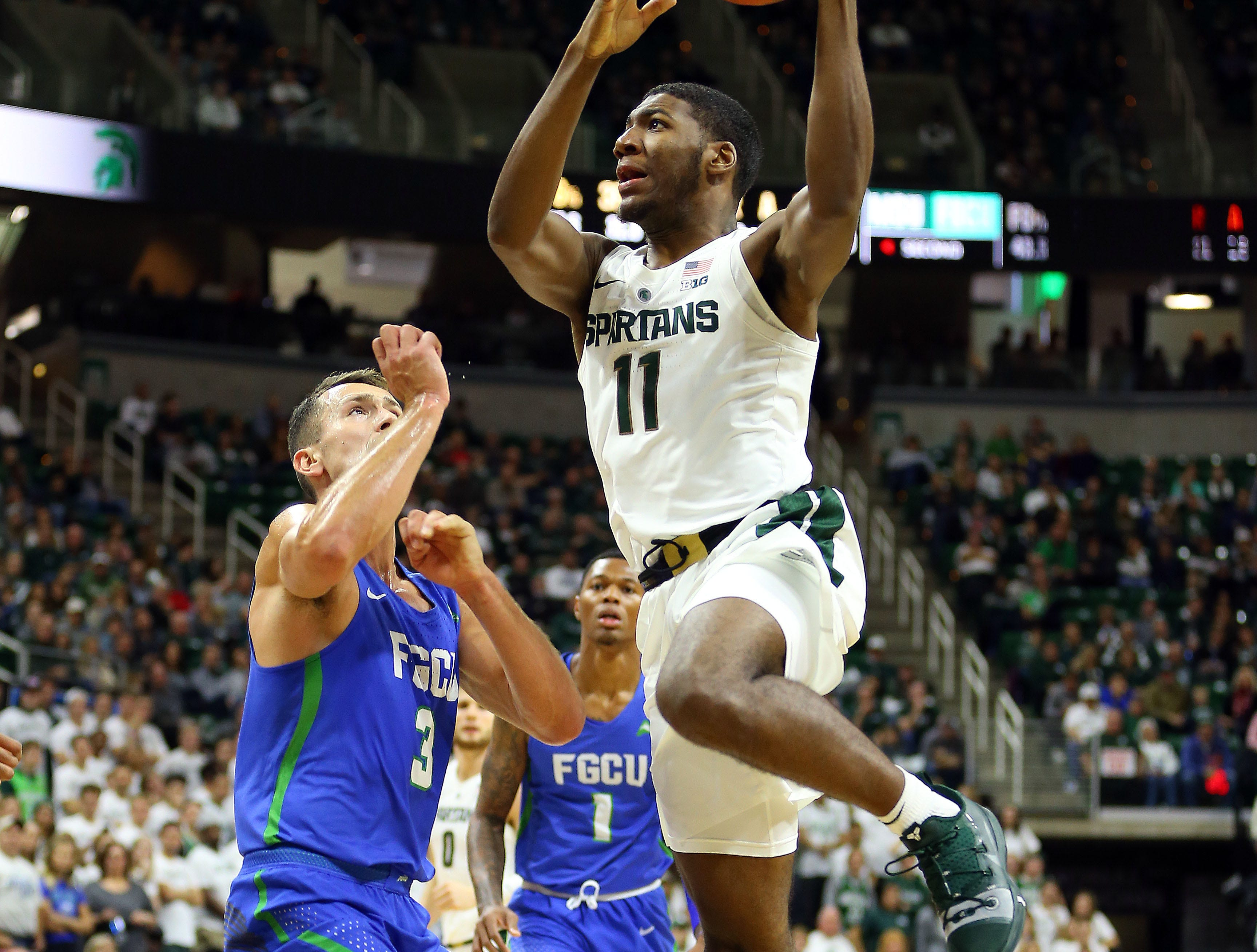 Nov 11, 2018; East Lansing, MI, USA; Michigan State Spartans forward Aaron Henry (11) drives to the basket over Florida Gulf Coast Eagles guard Christian Carlyle (3) during the second half of a game at the Breslin Center. Mandatory Credit: Mike Carter-USA TODAY Sports