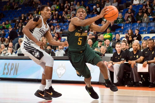 Nov 24, 2017; Portland, OR, USA; Michigan State Spartans guard Cassius Winston (5) drives past Connecticut Huskies guard Christian Vital (1) for a basket during the second half in a game at Veterans Memorial Coliseum. Michigan State beat Connecticut 77-57. Mandatory Credit: Troy Wayrynen-USA TODAY Sports