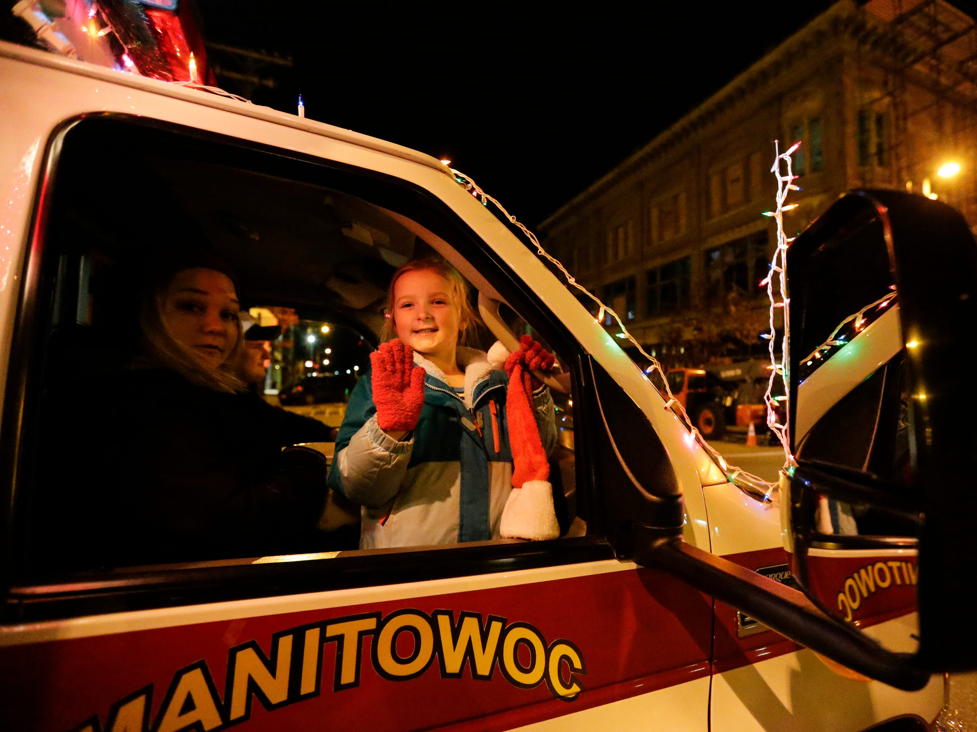 """A little girl waves from the Manitowoc ambulance during the 30th Annual Lakeshore Holiday Parade Wednesday, November 21, 2018, in Manitowoc, Wis. This year's theme was """"Christmas Through the Decades."""" Joshua Clark/USA TODAY NETWORK-Wisconsin"""