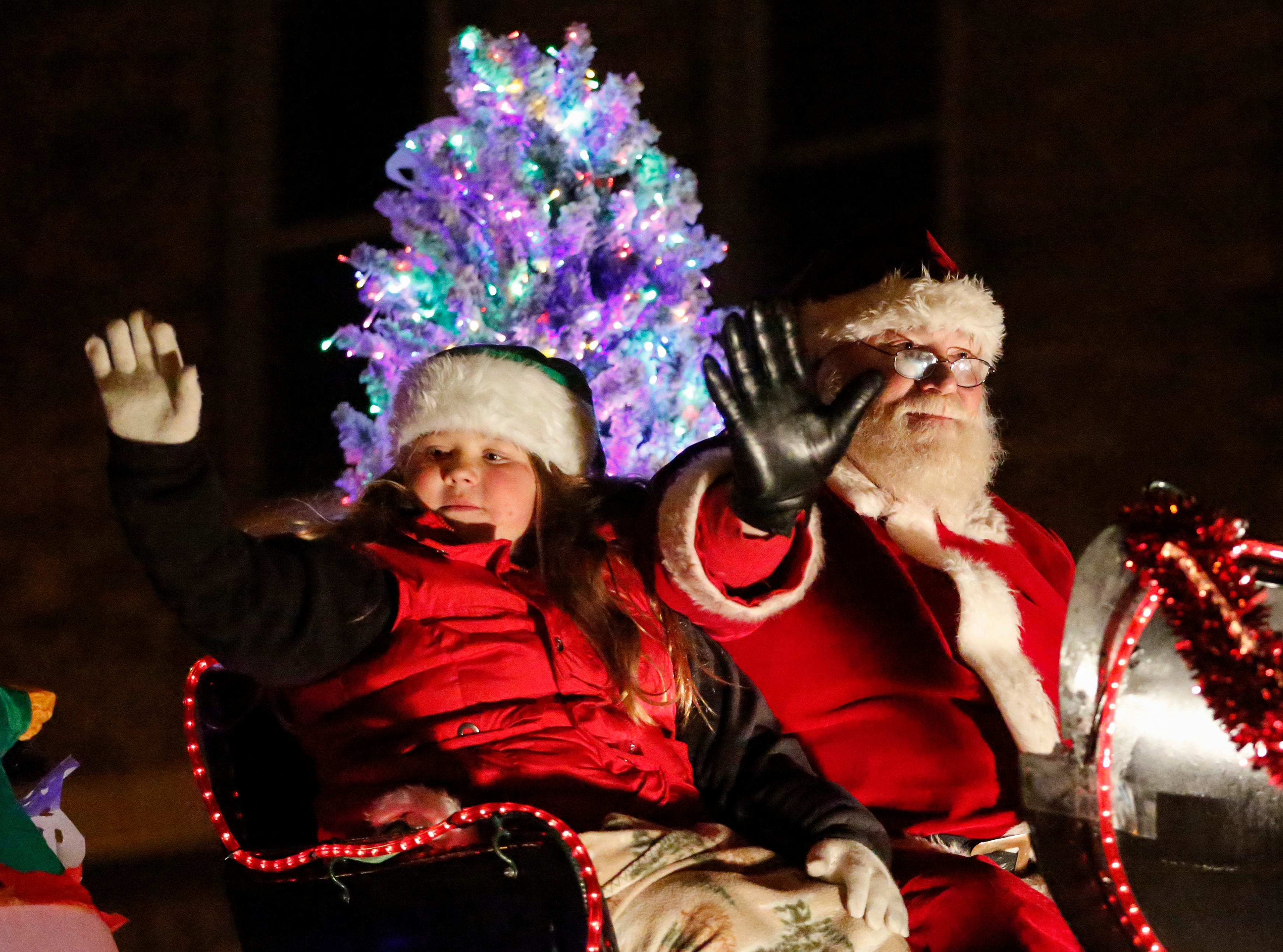 """Santa and one of his little helpers waive to the crowd during the 30th Annual Lakeshore Holiday Parade Wednesday, November 21, 2018, in Manitowoc, Wis. This year's theme was """"Christmas Through the Decades."""" Joshua Clark/USA TODAY NETWORK-Wisconsin"""