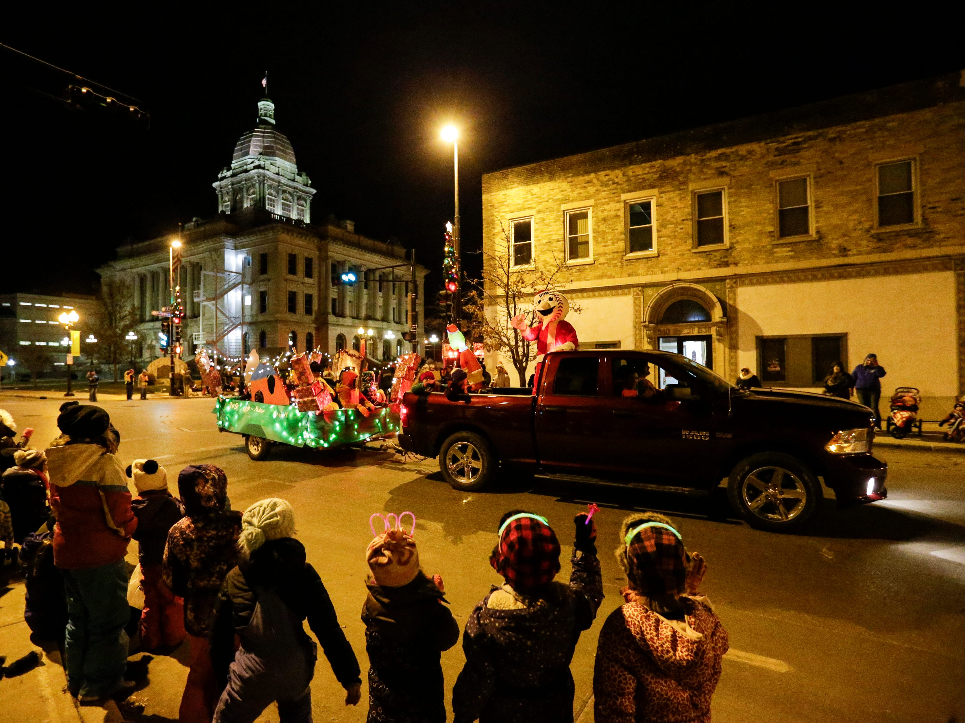 """Homer, the Miracle League mascot, waves to children during the 30th Annual Lakeshore Holiday Parade Wednesday, November 21, 2018, in Manitowoc, Wis. This year's theme was """"Christmas Through the Decades."""" Joshua Clark/USA TODAY NETWORK-Wisconsin"""