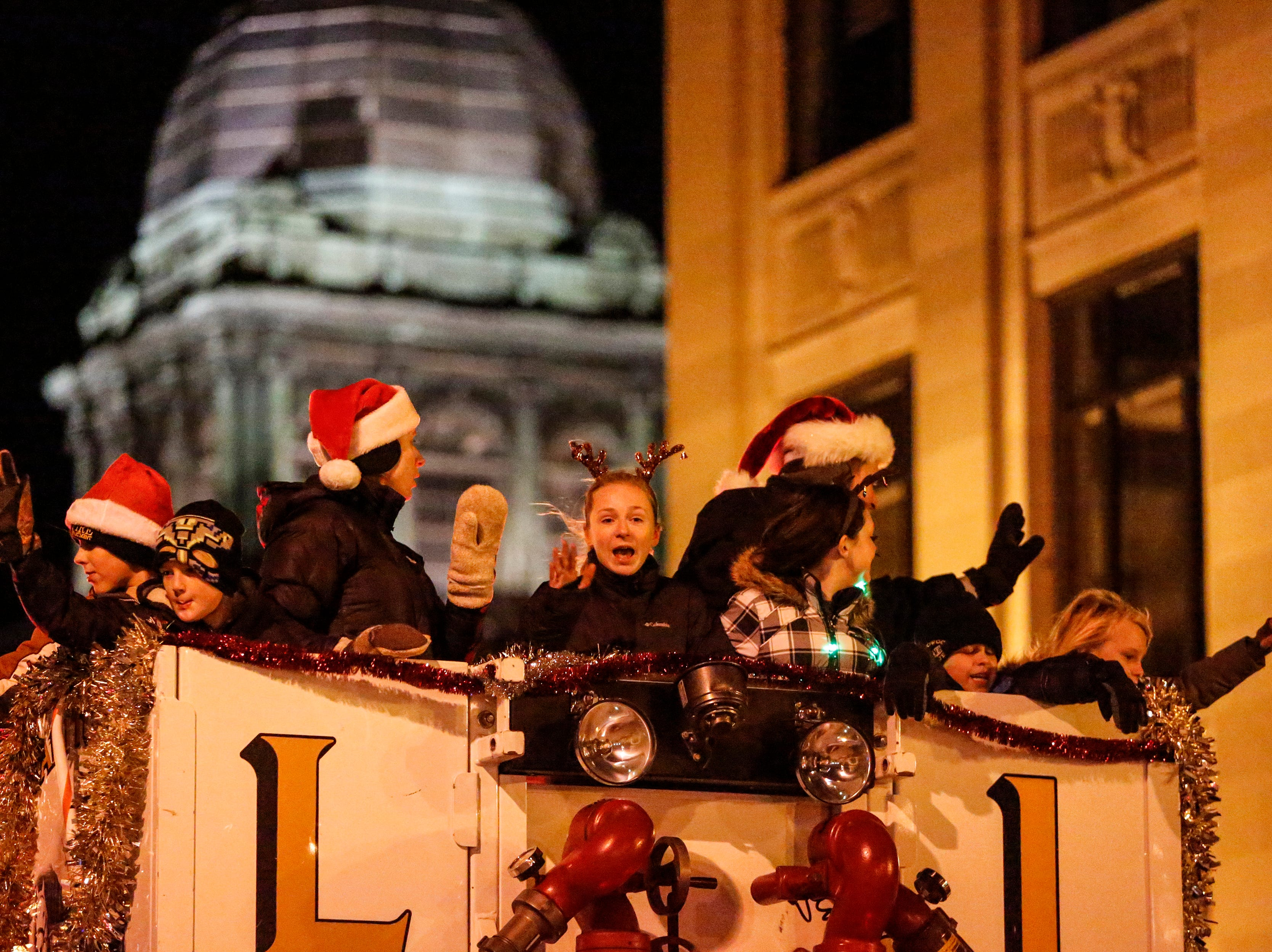 """Families waive to the crowd from the Manitowoc Fire Department bucket lift during the 30th Annual Lakeshore Holiday Parade Wednesday, November 21, 2018, in Manitowoc, Wis. This year's theme was """"Christmas Through the Decades."""" Joshua Clark/USA TODAY NETWORK-Wisconsin"""