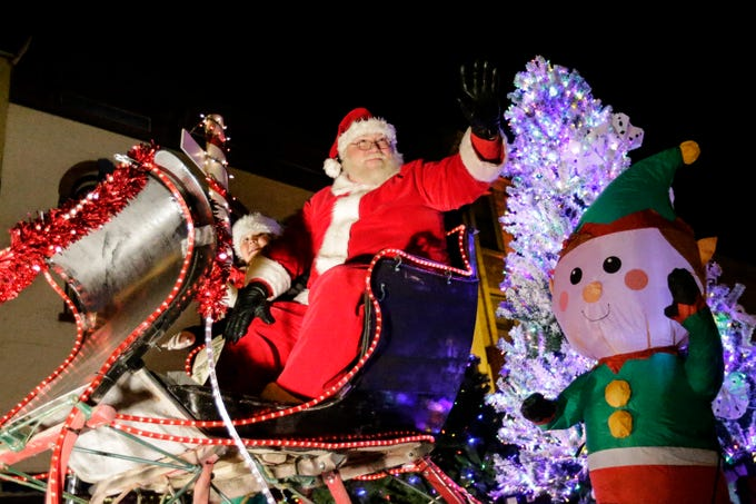 """Santa waves to the children from his sleigh during the 30th Annual Lakeshore Holiday Parade Wednesday, November 21, 2018, in Manitowoc, Wis. This year's theme was """"Christmas Through the Decades."""" Joshua Clark/USA TODAY NETWORK-Wisconsin"""
