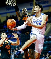 Memphis center Isaiah Maurice (right) drives for a layup against Oklahoma State deferrer Cameron McGriff (back) during first round action in the Advocate Invitational in Orlando Thursday, November 22, 2018.