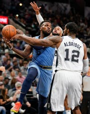 Memphis Grizzlies' Shelvin Mack (6) looks to pass as he is pressured by San Antonio Spurs' LaMarcus Aldridge (12) and Patty Mills during the first half of an NBA basketball game Wednesday, Nov. 21, 2018, in San Antonio. (AP Photo/Darren Abate)