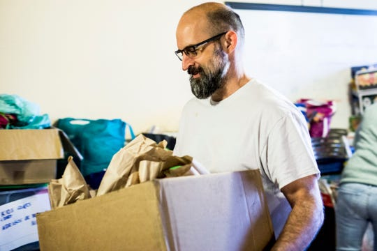 November 22 2018 - Lee Coleman moves a box of packed lunches while volunteering for the Migration is Beautiful aid group at First Congregational Church in the Cooper Young neighborhood. Volunteers spent the morning packing sandwiches, snacks and other necessities for migrants at Memphis' Greyhound terminal.