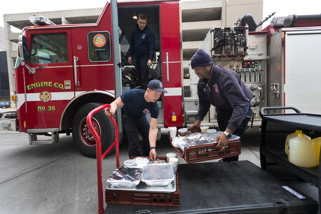 Firefighters Mitch Garcia (left), Jared Triplett (right) and Joel Alone load their truck with complete Thanksgiving dinners for their station at Fiserv Forum in Milwaukee, Wis. About 40 employees of Levy Restaurants and the Milwaukee Bucks made Thanksgiving dinner for all the Milwaukee fire stations. They are from Engine Co. 36 at N. 27th St. and W. Capitol Dr.