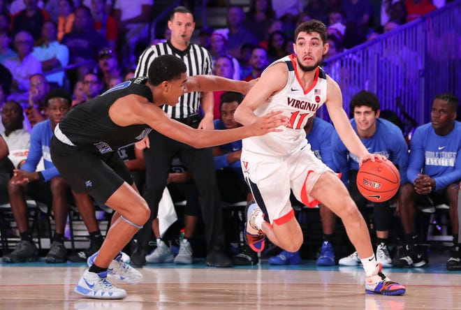 Nov 21, 2018; Paradise Island, BAHAMAS; Virginia Cavaliers guard Ty Jerome (11) dribbles as Middle Tennessee Blue Raiders guard Anthony Crump (0) defends during the first half at Imperial Arena.