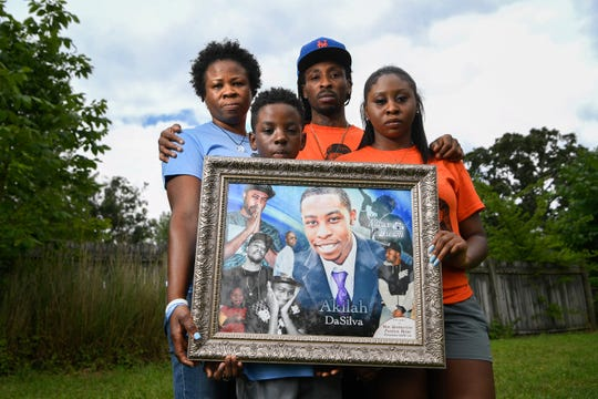 Akilah DaSilva's family holds a portrait of him.