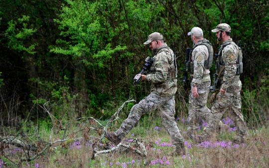 ATF personnel search a wooded area Monday, April 23, 2018, near Burnette Chapel Church of Christ, scene of the 2017 Antioch church shooting, for the man who shot and killed four people the day before at a nearby Waffle House. Suspect Travis Reinking was captured after a 34-hour manhunt.