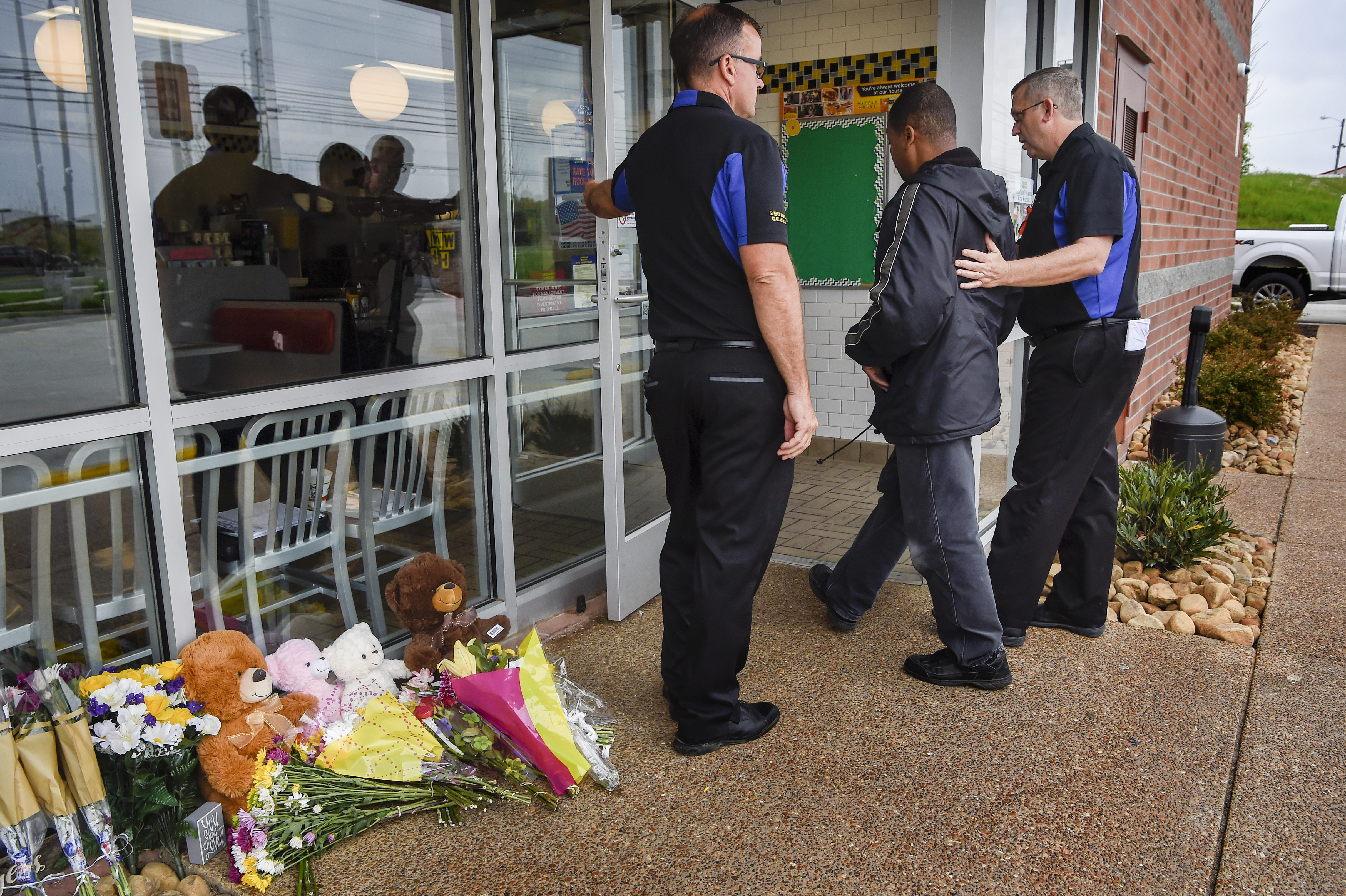 Jeff Camp and Ken Wright of Waffle House escort Ronald Page into the reopened restaurant three days after the deadly shooting.
