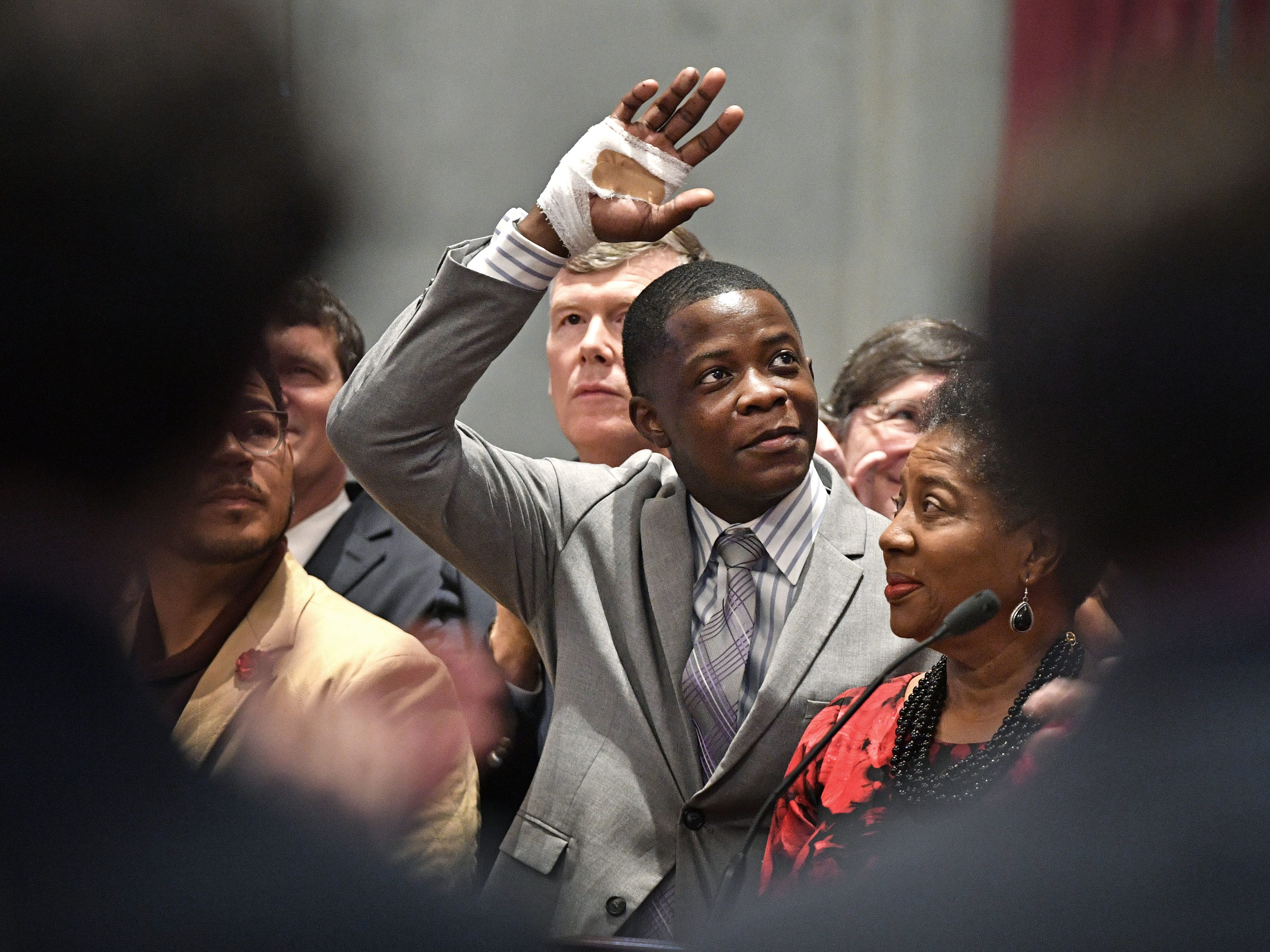Sacrifice: James Shaw Jr. waves to the crowd and legislators inside the House chambers as he was honored for disarming a shooter inside an Antioch Waffle House Tuesday April 24, 2018, in Nashville, Tenn.