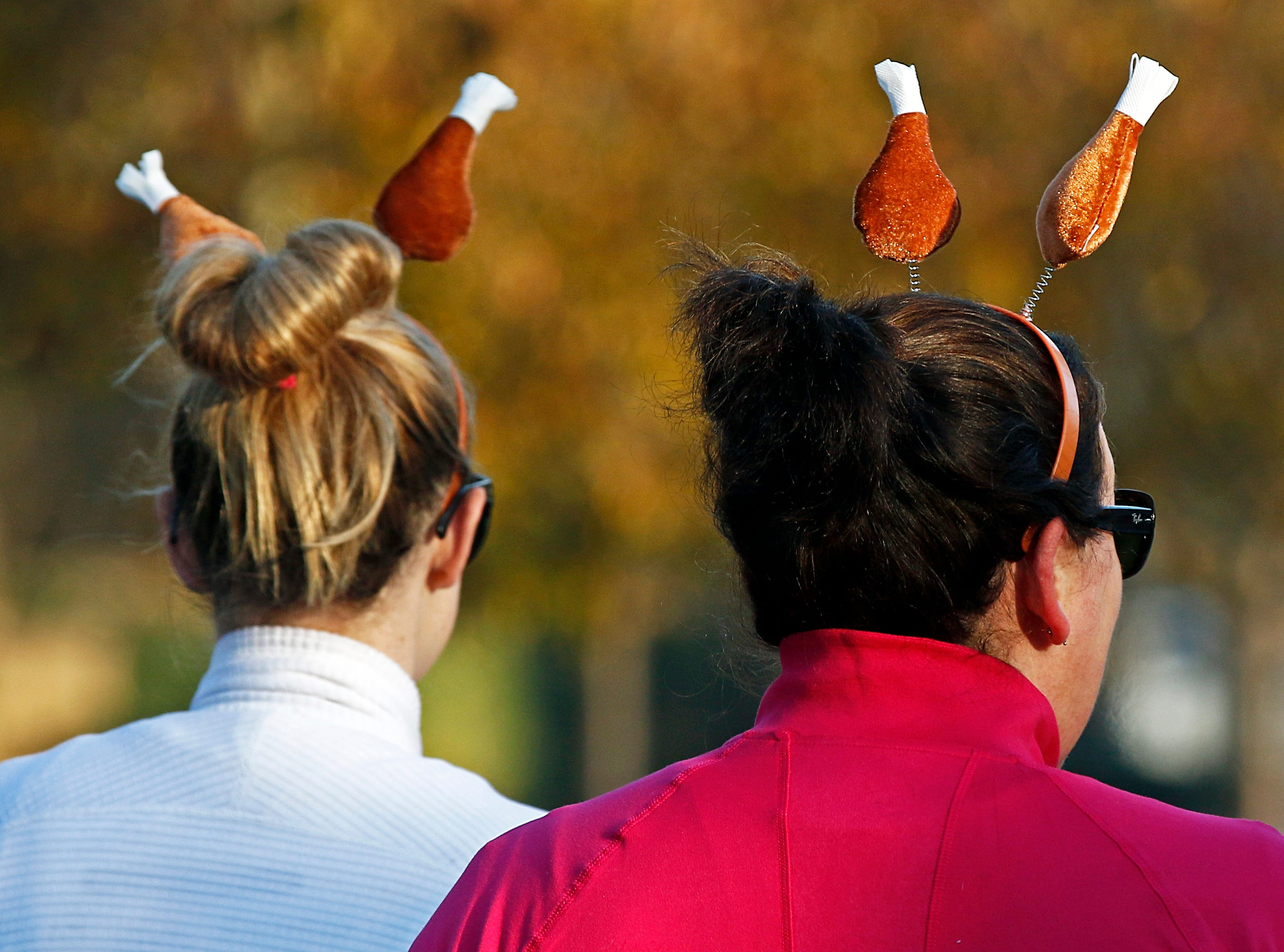 Two runners wearing turkey legs make their way to the starting line before the annual Boulevard Bolt Thursday, Nov. 22, 2018, in Nashville, TN.
