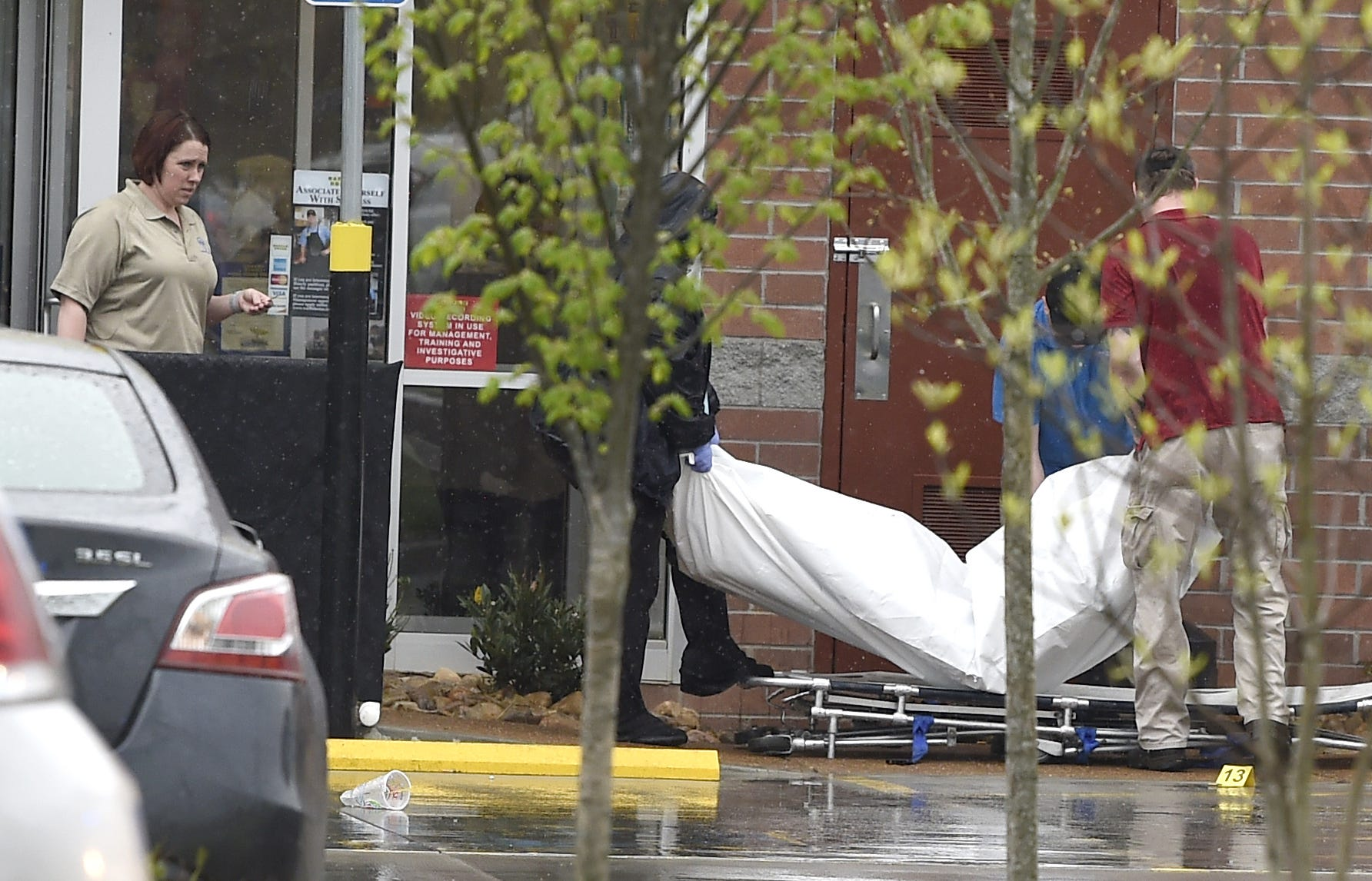 Coroners carry a body from the scene where four died after a gunman opened fire at a Waffle House in Antioch.