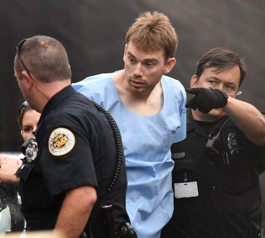 Law enforcement personnel escort Waffle House shooting suspect Travis Reinking into booking Monday, April 23, 2018, at Hill Detention Center in Nashville.