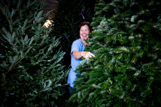 Wynne Ridgway laughs as she wraps her arms around a Christmas tree, trying to figure out if it's the right one, on Thursday, November 22, 2018, at Heath Christmas Trees in Naples. Ridgway has been coming to get trees from Heath since they opened shop in Naples about forty years ago and says the owners always know what she's looking for.