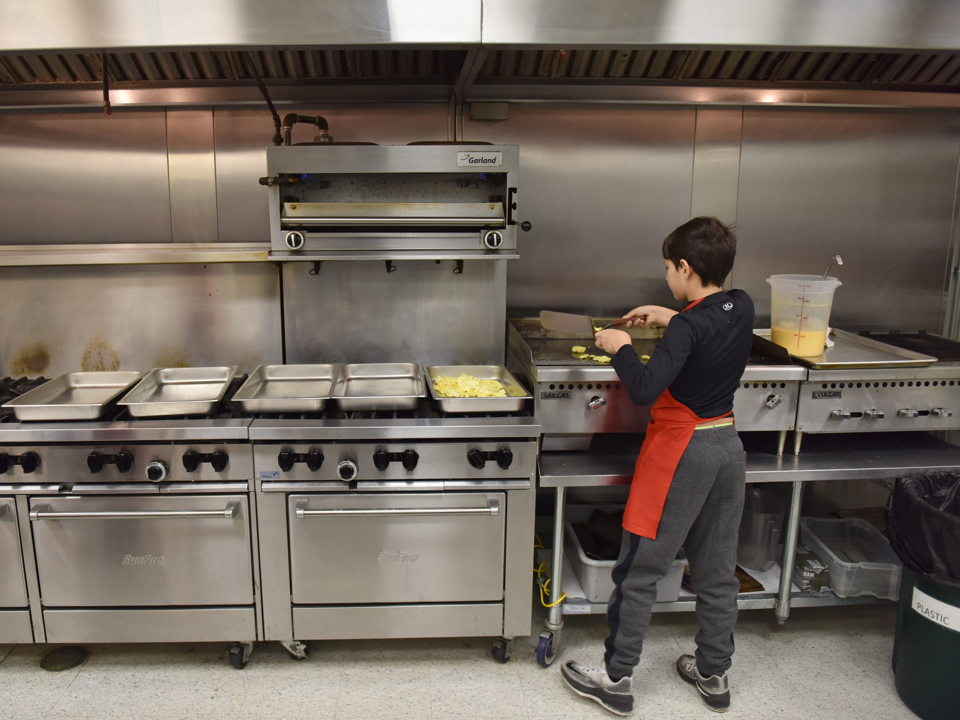 Cole Rosica, 11, a volunteer, helps the Salvation Army and Eastwick College prepares scrambled eggs in the kitchen for the Thanksgiving breakfast in Hackensack on Thursday morning November 22, 2018.