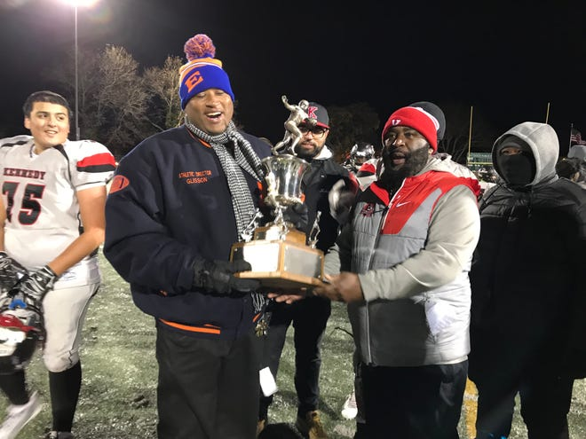 Eastside athletic director Gerald Glisson awards a trophy to Kennedy coach Ron Jackson after their rivalry football game in 2018.