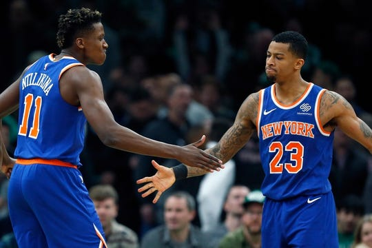 New York Knicks' Frank Ntilikina (11) and Trey Burke (23) react after a defensive play during the second half on an NBA basketball game against the Boston Celtics in Boston, Wednesday, Nov. 21, 2018.