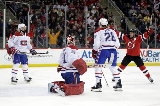 New Jersey Devils left wing Taylor Hall, right, celebrates after scoring a goal on Montreal Canadiens goaltender Carey Price (31) during the second period of an NHL hockey game Wednesday, Nov. 21, 2018, in Newark, N.J. (AP Photo/Julio Cortez)