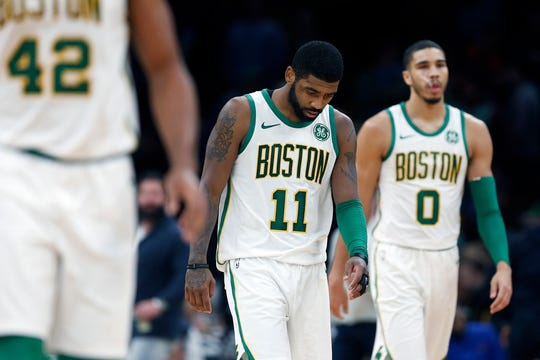 Boston Celtics' Kyrie Irving (11) and Jayson Tatum (0) walk up court during the second half on an NBA basketball game against the New York Knicks in Boston, Wednesday, Nov. 21, 2018.