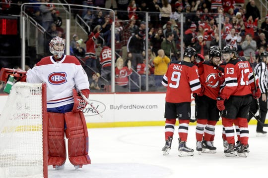 Montreal Canadiens goaltender Carey Price, left, stands near his net after allowing a goal to New Jersey Devils left wing Taylor Hall (9) during the second period of an NHL hockey game Wednesday, Nov. 21, 2018, in Newark, N.J. (AP Photo/Julio Cortez)