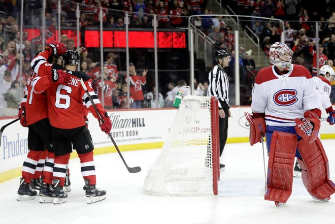 New Jersey Devils, left, celebrate a goal by center Pavel Zacha (37) as Montreal Canadiens goaltender Carey Price, right, skates away during the second period of an NHL hockey game Wednesday, Nov. 21, 2018, in Newark, N.J. (AP Photo/Julio Cortez)