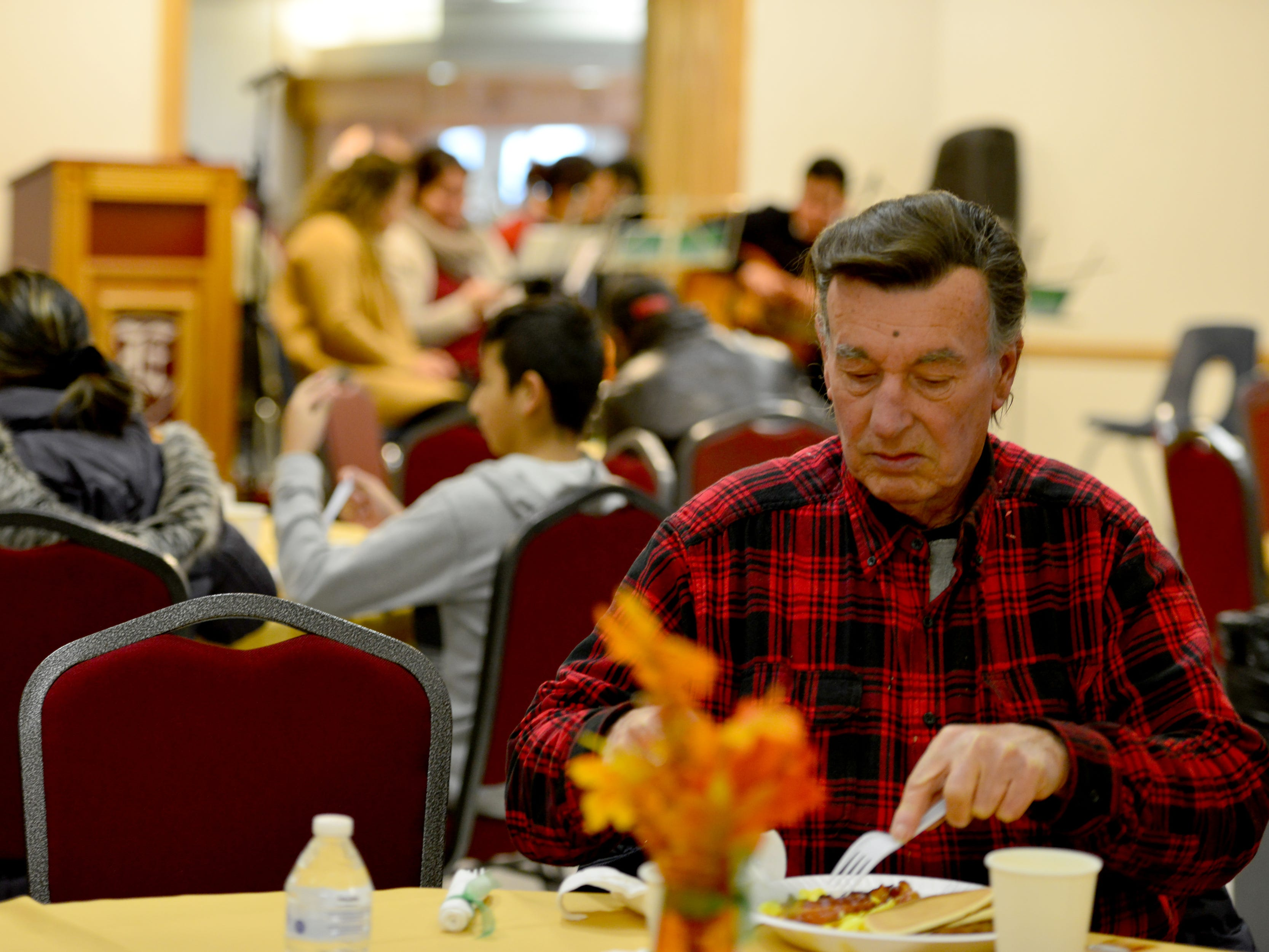 John Lozier, of Hackensack, east breakfast as a band plays holiday music in the background at Eastwick College, which is serving breakfast on Thanksgiving day with the Salvation Army in Hackensack on Thursday morning November 22, 2018.