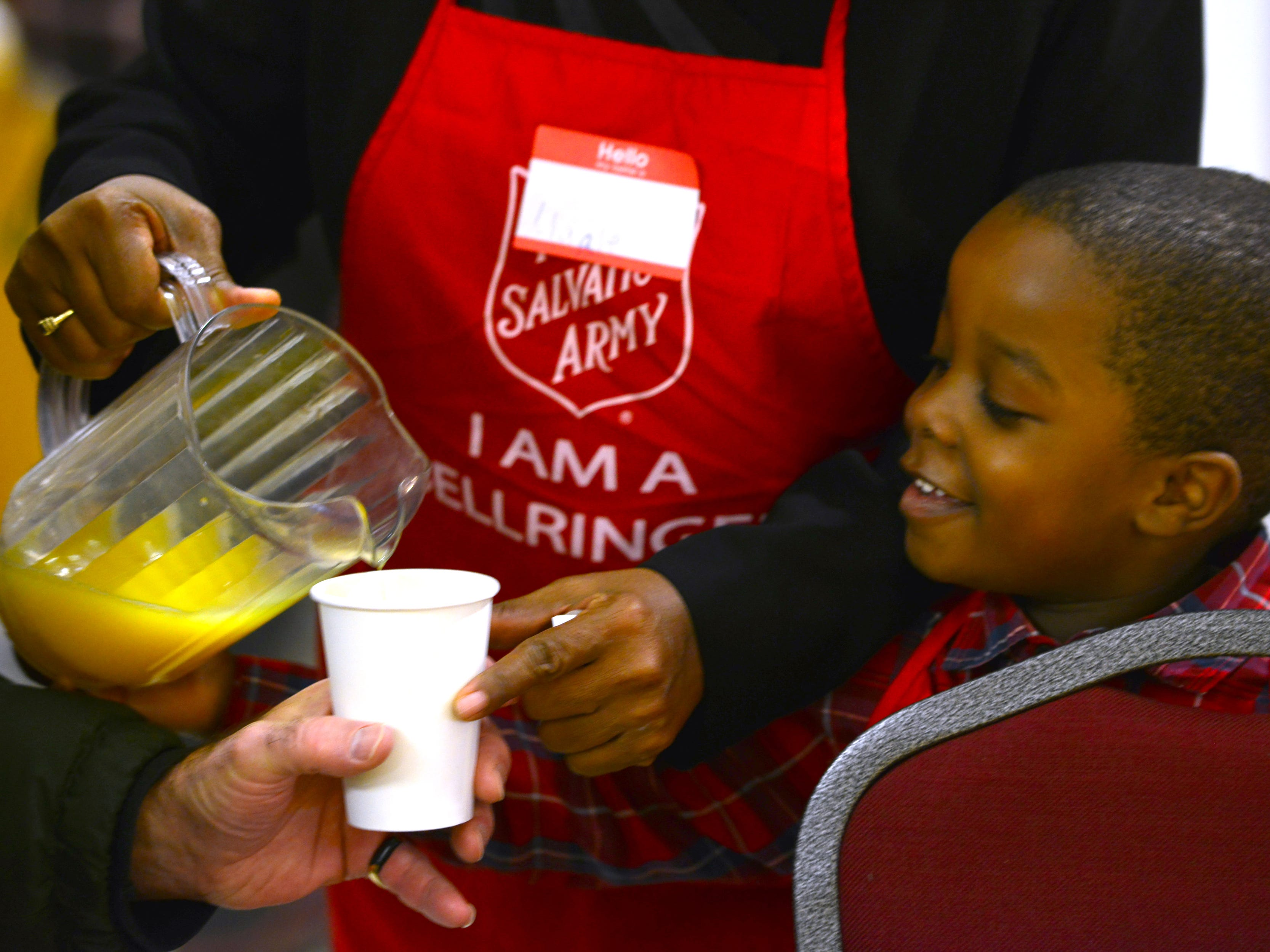 Noah Neal, 5, helps his grandmother, serve orange juice at the Thanksgiving breakfast at Eastwick College in Hackensack on Thursday morning November 22, 2018.
