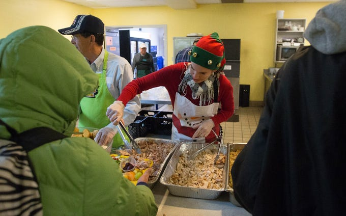 Teri Howard, serves turkey to a homeless client of El Caldito Soup Kitchen, Thursday November 22, 2018 during the soup kitchen's Thanksgiving dinner.