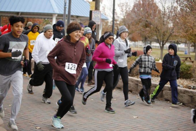 Runners start the 5k Gratitude Run, Thursday, Nov. 22, 2018, in Berg Park in Farmington.