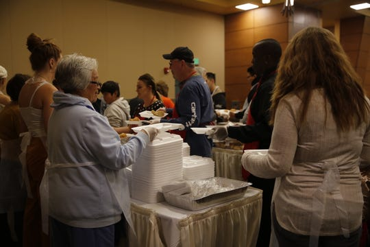 Volunteers serve meals Thursday during the annual Thanksgiving dinner at the Farmington Civic Center.