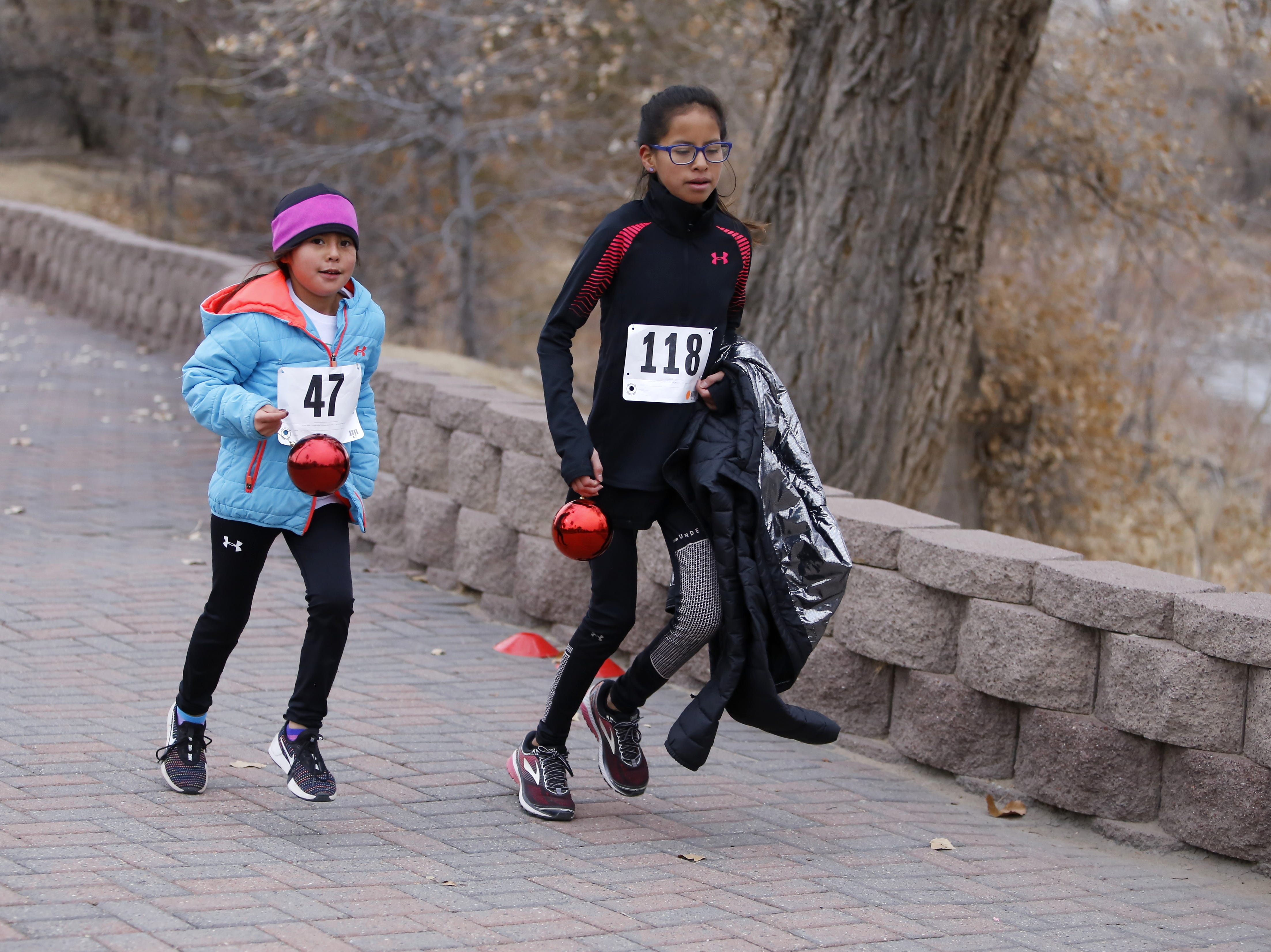 Kailyn Lake, 7, and Adrianna Lake, 12, reach the finish line, Thursday, Nov. 22, 2018, with items they found along the trail. The ornaments were hidden for Gratitude Run participants to find. The sisters received prizes for finding the ornaments.