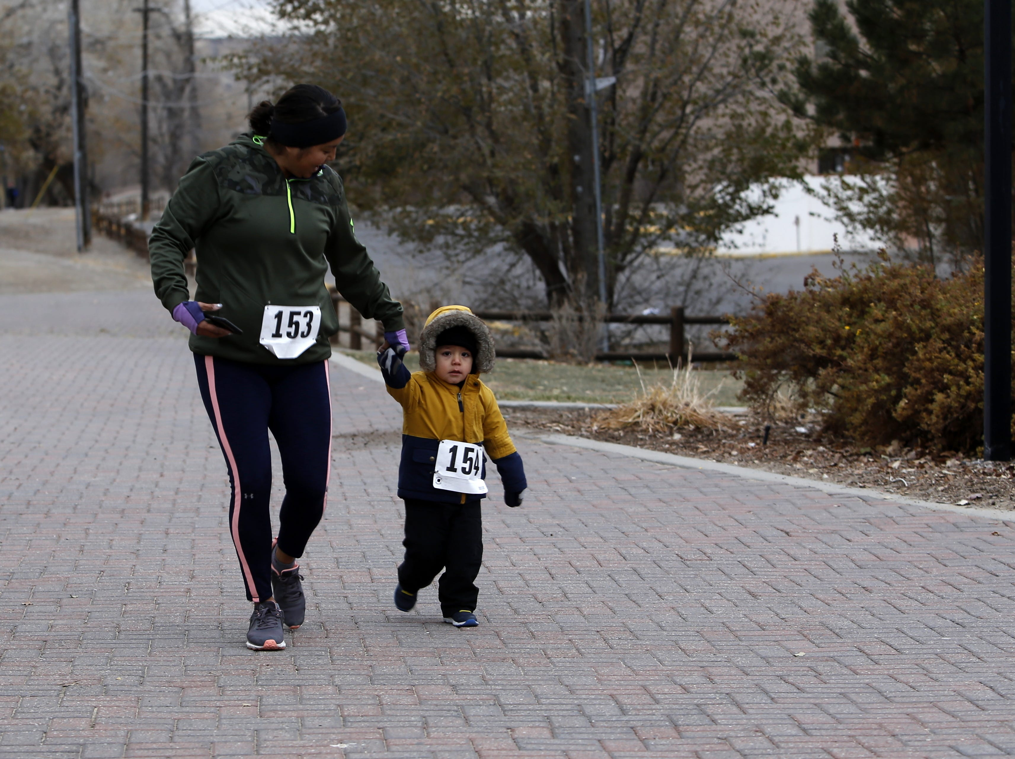 Tasha Cloyd and Logan, 2, participate in the Gratitude Run, Thursday, Nov. 22, 2018, in Berg Park in Farmington.