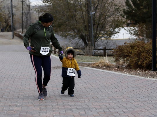 Tasha Cloyd and Logan, 2, participate in the Gratitude Run Thursday in Berg Park in Farmington.