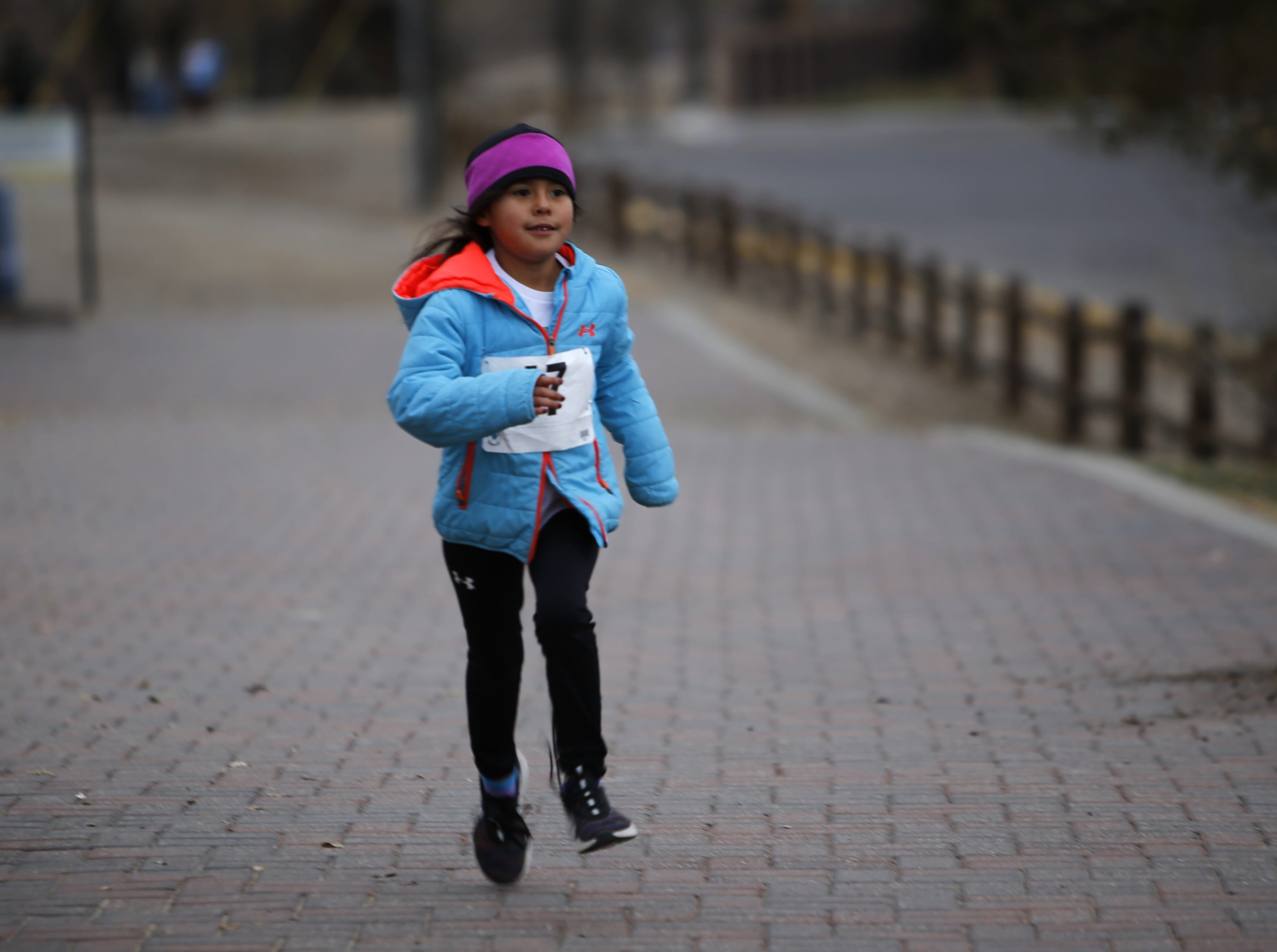 Kailyn Lake, 7, runs a 400-meter children's race during the Gratitude Run, Thursday, Nov. 22, 2018, in Berg Park in Farmington.