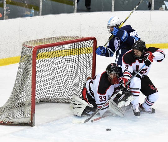 Churchill goalie Bryant Riley (33) tries to cover up in frot of teammate Luc Greener (8) as Stevenson's Ethan Waldo crashes the net.