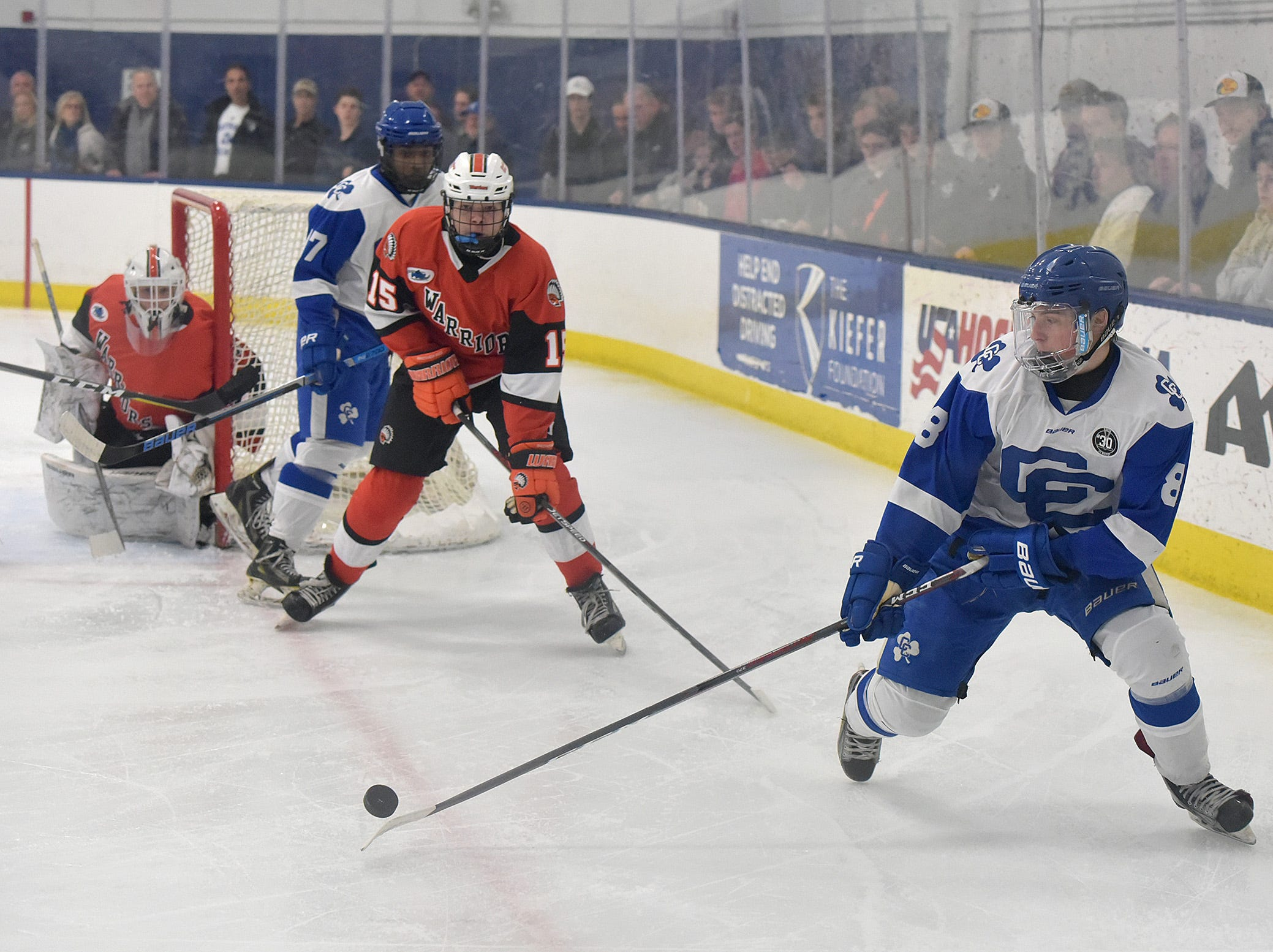 CC's Joe Bothwick moves the puck from behind the Rice goal. Brother Rice defenseman Nick Dippre (15) and CC forward Rylan Clemons (17) follow the puck.