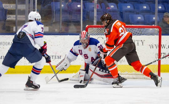 U.S. NTDP Under-18 goalie Spencer Knight (30) corrals a loose puck with help from defenseman Alex Vlasic (7) Wednesday, Nov. 21 at USA Hockey Arena. At right for Bowling Green is Connor Ford (20).