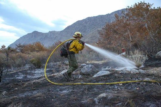 Rachel Boot with the U.S. Forest Service extinguishes hot spots from a brush fire that started on Tramway Rd. in Palm Springs, November 21, 2018.