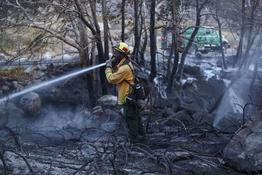 Felix Cunningham with the U.S. Forest Service extinguishes hot spots from a brush fire that started on Tramway Rd. in Palm Springs, November 21, 2018.