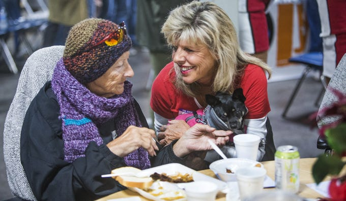 Volunteer Kim Accurso, right, speaks with Michelle La Page as she holds Michelle's dog, Tio, at the Thanksgiving Day meal served by volunteers with the St. Vincent de Paul Society. Hundreds enjoyed turkey, mashed pototaoes and pumpkin pie at the Human Services Campus Dining Room in Phoenix, Thursday, November 22, 2018.